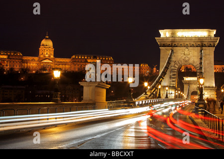 Traffic at the Chain Bridge and the Royal palace of Buda in Budapest, Hungary by night - Stock Photo