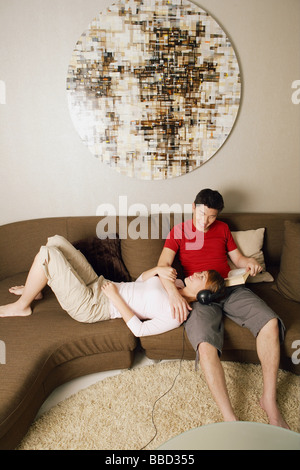 Couple at home, woman lying on man's lap - Stock Photo