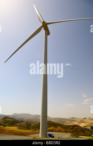Single wind turbine tower with car parked next to base to show massive size of the turbine structure - Stock Photo