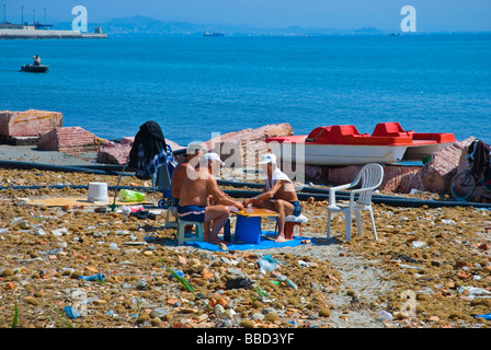 People playing a boardgame on a dirty beach in Durres Albania Europe - Stock Photo