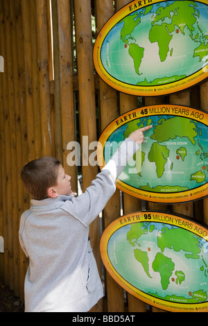 A young boy pointing at England on a map at Edinburgh Zoo, Scotland, UK - Stock Photo
