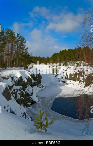 Water cascade between the grey rocks in winter season. Blue sky with clouds. Pines on the stones are covered by - Stock Photo