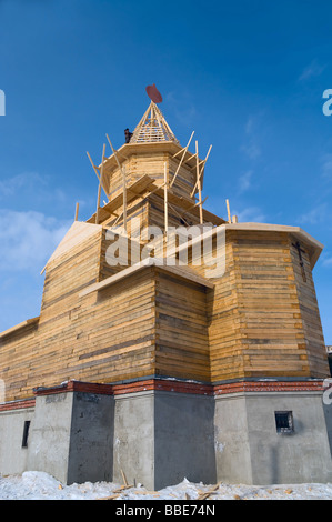Wooden church from squared beam under construction on the blue sky background. Full size building. Segezha, Karelia, - Stock Photo