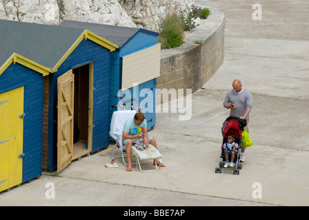 Broadstairs, Kent, England, UK. Louisa Bay. Man with child in pushchair walking past man by beach huts - Stock Photo