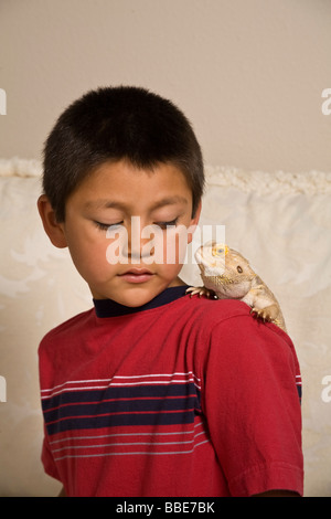 Portrait of young Hispanic boy 6=9 year old olds age looking at Bearded Dragon on shoulder closeup light background - Stock Photo