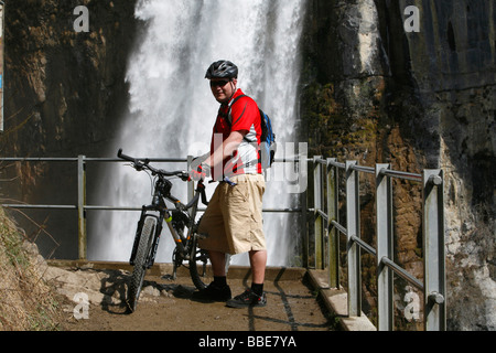 Biker marvels at the thundering waterfalls of Rinquelle, Rin Spring, and Seerenbach, Betlis, St. Gallen, Switzerland, - Stock Photo