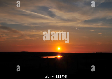 The orb of a red suns shines on the distant waters of the Warley Moor Reservoir, at Fly Flats, on the moors north of Halifax, UK Stock Photo