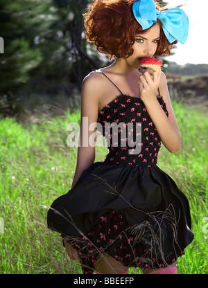 Woman eating cupcake - Stock Photo