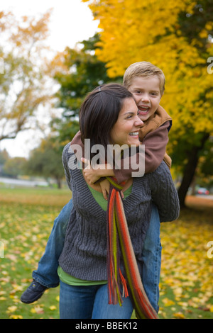 Little Boy Getting a Piggyback Ride From His Mother, Portland, Oregon, USA - Stock Photo