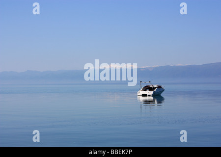 A motorboat on Ohrid Lake, Macedonia, with Albania in the background - Stock Photo