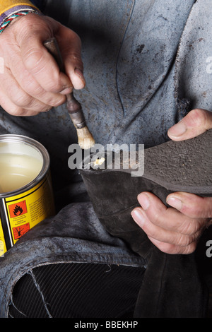 Close-up of Italian Shoemaker Applying Glue to Heel of Boot - Stock Photo