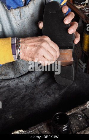 Close-up of Italian Shoemaker Applying Ink to Heel of Shoe - Stock Photo