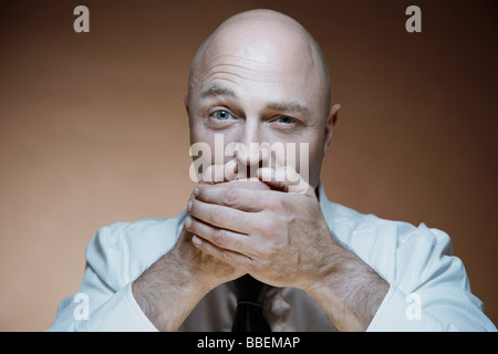 Portrait of Man Covering Mouth with Hands - Stock Photo