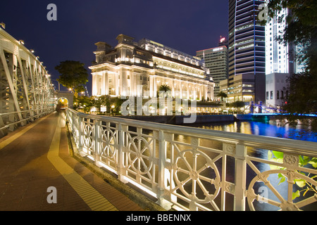 Cavenagh bridge Fullerton Hotel Skyline of Singapore  South East Asia twilight - Stock Photo