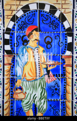 A ceramic wall decoration with a Tunisian man in traditional attire serving tea at Cafe Charbi Khemais in Sousse, - Stock Photo