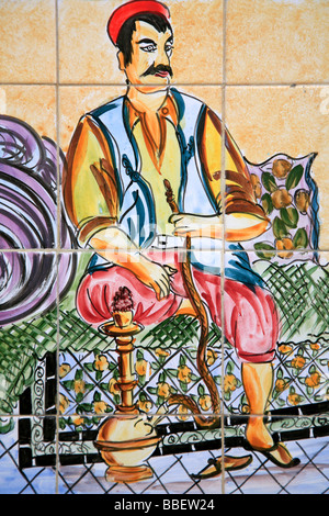 A ceramic wall decoration showing a Tunisian man in traditional attire smoking a waterpipe at Cafe Charbi Khemais - Stock Photo