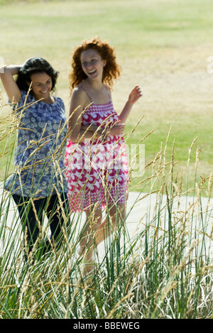 Two young women walking arm in arm outdoors, both laughing - Stock Photo