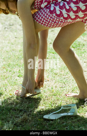 Young woman bending over to put on sandal, cropped - Stock Photo