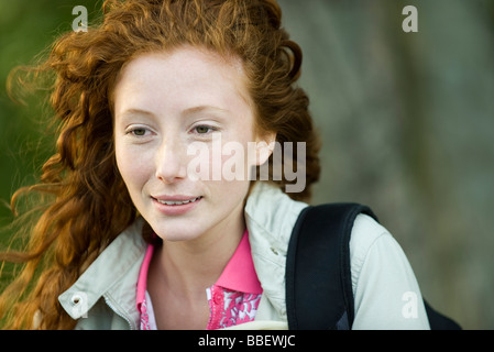 Young red haired woman outdoors, portrait - Stock Photo