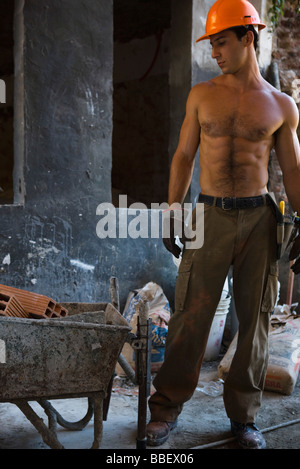 Barechested construction worker standing near wheelbarrow at construction site - Stock Photo