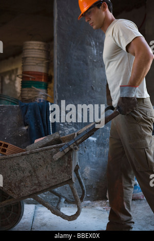 Construction worker pushing wheelbarrow through construction site - Stock Photo