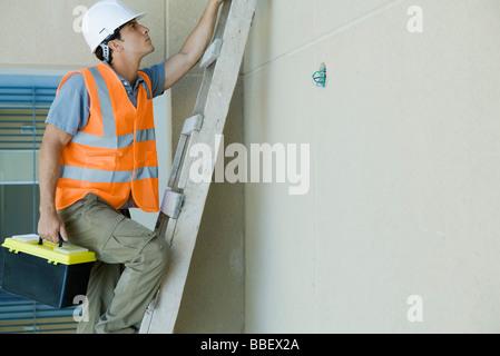 Man climbing ladder carrying toolbox - Stock Photo