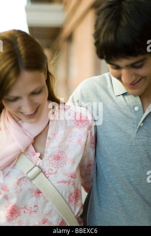 Young couple side by side, looking down, smiling - Stock Photo