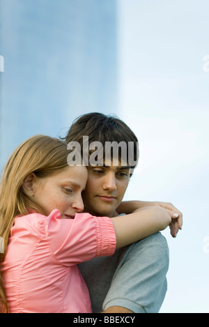 Young couple embracing, looking down - Stock Photo