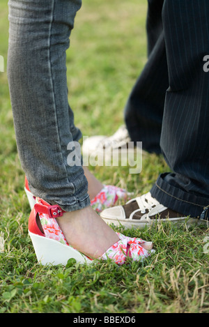 Young couple in trendy clothing standing face to face, low section - Stock Photo