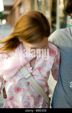 Young couple walking with arms around each other, cropped - Stock Photo