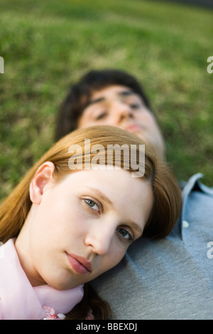 Young couple lying on ground, woman resting head on man's chest, looking at camera - Stock Photo