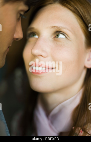 Young couple gazing into each other's eyes, smiling, close-up - Stock Photo