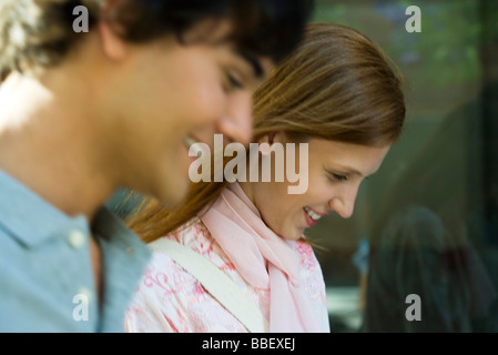 Young couple walking together outdoors, both smiling, looking down - Stock Photo