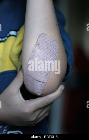 Young boy with a band aid on his arm - Stock Photo