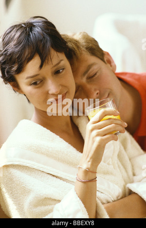 Woman wearing bathrobe and holding glass of juice, man resting head on her shoulder - Stock Photo