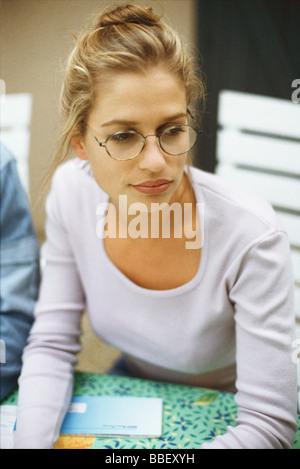 Blonde woman wearing glasses, looking away - Stock Photo