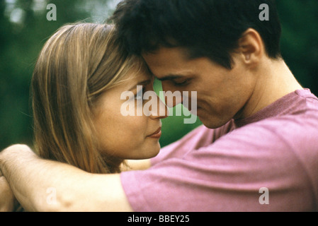 Couple embracing, touching foreheads, side view - Stock Photo