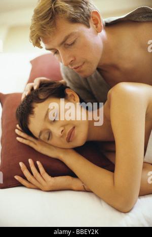 Couple in bed, man watching woman sleep - Stock Photo