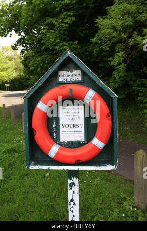 A life saving round ring or lifebelt situated at the edge of a river and weir - Stock Photo
