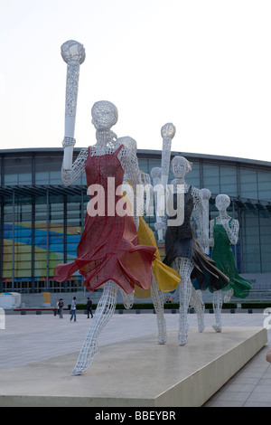 Female statues carrying the Olympic torch are seen outside the Beijing National Stadium in Beijing, China - Stock Photo
