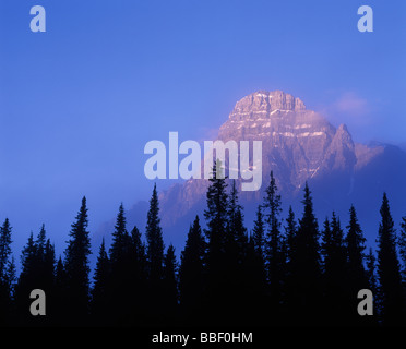 Fog lifting off forest floor over the surrounding mountain peaks of the Canadian Rockies Banff National Park Alberta - Stock Photo