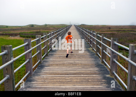 A child runs on a boardwalk into distance towards the sea - Stock Photo