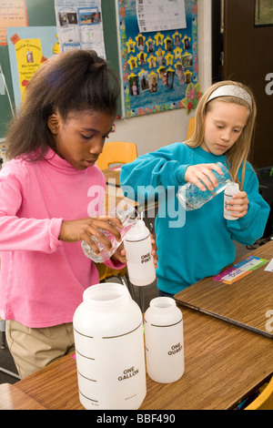 Two school children 8-9 year old working together pour fluid multi ethnic racial  racially diverse multicultural - Stock Photo