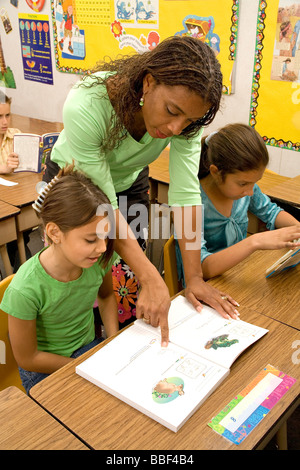 racial diversity racially diverse multicultural multi cultural Teacher inter racial students 8-10 year old studying - Stock Photo