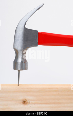 Hammer hitting a nail on the head into wood - Stock Photo