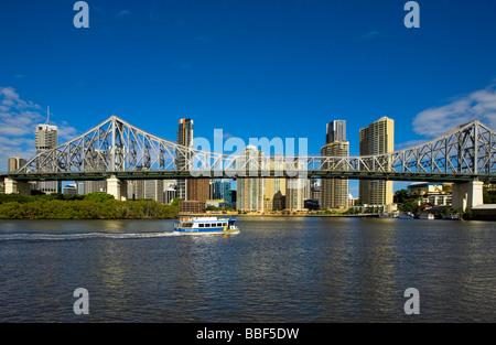 Australia, Queensland, Brisbane. City Ferry goes under the Story Bridge with Brisbane skyline - Stock Photo