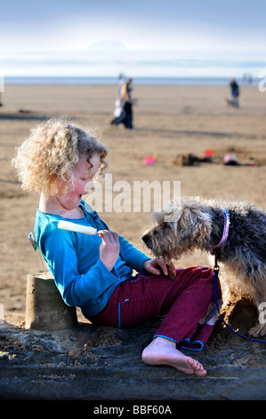 A YOUNG GIRL WITH AN ICE LOLLY AND PET DOG ON THE SEA WALL ON THE BEACH AT WESTON SUPER MARE SOMERSET UK - Stock Photo