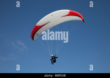 Paraglider coming into land cliffs Rhossili Bay The Gower South Wales UK - Stock Photo