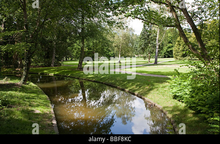 Canal and trees casting shade in water gardens park Schwerin Germany - Stock Photo