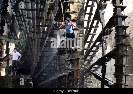 Boys jump off the waterwheels or Norias in Hama Syria - Stock Photo
